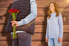 Composite image of man hiding roses behind back from woman. Man hiding roses behind back from woman against blue paint splashed surface Stock Photo