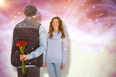 Composite image of man hiding roses behind back from woman. Man hiding roses behind back from woman against glowing background Royalty Free Stock Photography