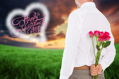 Composite image of man holding bouquet of roses behind back Stock Photo