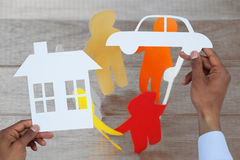 Composite image of man holding a car and a house in paper. Man holding a car and a house in paper against colorful paper figures forming circle on table Stock Image