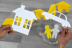 Composite image of man holding a car and a house in paper. Man holding a car and a house in paper against paper cutout figures standing in circle by paper houses Stock Image