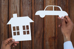 Composite image of man holding a car and a house in paper. Man holding a car and a house in paper against wood Royalty Free Stock Photography