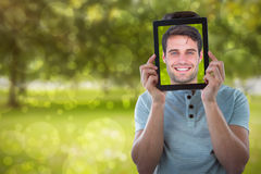 Composite image of man holding digital tablet in front of face Royalty Free Stock Photo