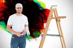 Composite image of man holding paint roller while standing by ladder Stock Images
