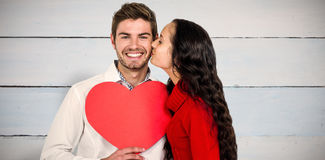 Composite image of man holding paper heart and being kissed by girlfriend Stock Photo