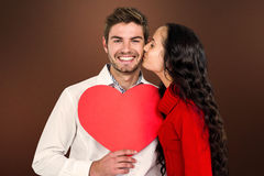 Composite image of man holding paper heart and being kissed by girlfriend Royalty Free Stock Photography