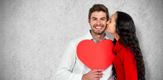 Composite image of man holding paper heart and being kissed by girlfriend Stock Photography