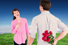 Composite image of man holding roses behind him Stock Photography
