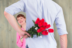 Composite image of man holding roses behind him Royalty Free Stock Photos