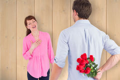 Composite image of man holding roses behind him Stock Photos