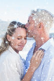 Composite image of man kissing his smiling partner on the forehead at the beach Royalty Free Stock Photos