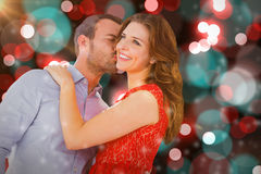 Composite image of man kissing woman on cheek. Man kissing woman on cheek against digitally generated twinkling light design Stock Photos