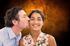 Composite image of man kissing woman on the cheek Royalty Free Stock Image