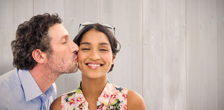 Composite image of man kissing woman on the cheek Royalty Free Stock Photography
