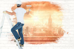 Composite image of man on ladder painting with roller Stock Photos