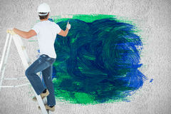 Composite image of man on ladder painting with roller Stock Images