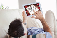 Composite image of man laying on sofa using a tablet pc Royalty Free Stock Images