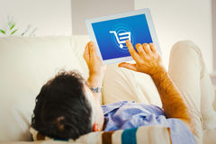 Composite image of man laying on sofa using a tablet pc Royalty Free Stock Photography