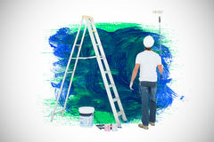 Composite image of man with paint roller standing by ladder Royalty Free Stock Image