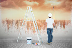 Composite image of man with paint roller standing by ladder Stock Images