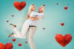 Composite image of man picking up his partner while hugging here Royalty Free Stock Images