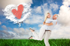 Composite image of man picking up his partner while hugging here Stock Photo
