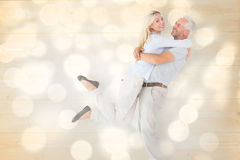 Composite image of man picking up his partner while hugging here Royalty Free Stock Photos