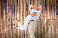 Composite image of man picking up his partner while hugging here Royalty Free Stock Photo