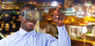 Composite image of man pointing while wearing virtual reality headset against illuminated city Royalty Free Stock Image