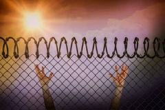 Composite image of man posing with arms raised. Man posing with arms raised against barbed wire fence by white background Royalty Free Stock Photos