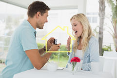 Composite image of man proposing marriage to his shocked blonde girlfriend Royalty Free Stock Images