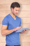 Composite image of man scrolling through tablet pc Royalty Free Stock Image