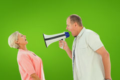 Composite image of man shouting at his partner through megaphone Royalty Free Stock Photos