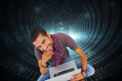 Composite image of man sitting on floor using laptop and smiling at camera Royalty Free Stock Images