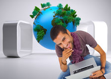 Composite image of man sitting on floor using laptop and smiling at camera Stock Photos