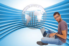 Composite image of man sitting using laptop and looking at camera Royalty Free Stock Images