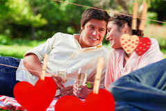 Composite image of man smiling as he looks at his friend during a picnic Royalty Free Stock Photo