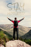 Composite image of man standing at hill top cheering. Man standing at hill top cheering against stay motivated Stock Photography