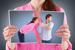 Composite image of man stopping woman from kissing. Man stopping women from kissing against grey vignette Royalty Free Stock Photos