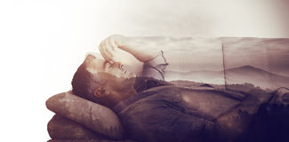Composite image of man suffering from headache while on sofa. Man suffering from headache while on sofa against trees and mountain range against cloudy sky Stock Photography