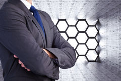 Composite image of man in a suit with folded arms Royalty Free Stock Photos