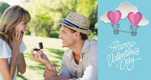 Composite image of man surprising his girlfriend with a proposal in the park Royalty Free Stock Images