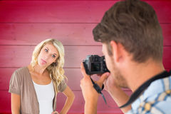 Composite image of man taking photo of his girlfriend sticking her tongue out Stock Photo