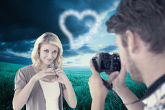 Composite image of man taking photo of his pretty girlfriend Stock Image
