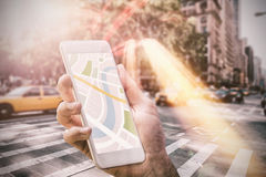 Composite image of man using map app on phone. Man using map app on phone against new york street Stock Images