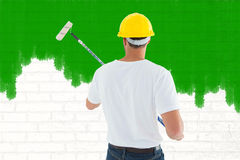 Composite image of man using paint roller Royalty Free Stock Photo