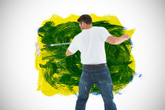 Composite image of man using paint roller on white background Royalty Free Stock Photos