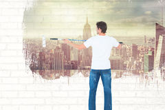 Composite image of man using paint roller on white background Royalty Free Stock Photo