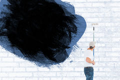 Composite image of man using paint roller on white background Stock Images