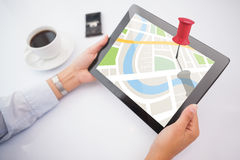 Composite image of man using tablet pc. Man using tablet pc against close-up of red pushpin Royalty Free Stock Image